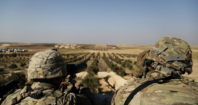 American troops look out toward the border with Turkey from a small outpost near the town of Manbij, northern Syria, Feb. 7.