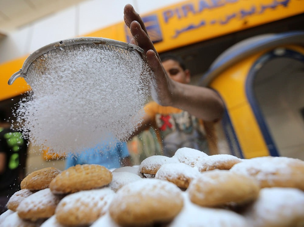 An Egyptian worker makes traditional sweets, Kahk, as part of the celebration of the Eid