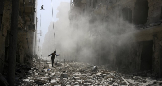A man walking on the rubble of damaged buildings after an airstrike on the moderate-held al-Qaterji neighborhood of Aleppo, Syria, Sept. 25, 2016.