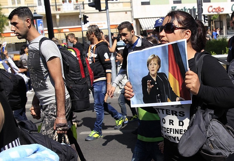 A womanl holds a picture of German Chancellor Angela Merkel as migrants set off on foot for the border with Austria from Budapest, Hungary, September 4, 2015. (Reuters Photo)