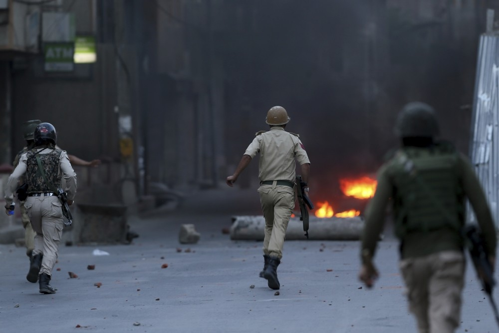 Indian policemen chase Kashmiri protesters during a protest, Srinagar, Indian controlled Kashmir, June 21.