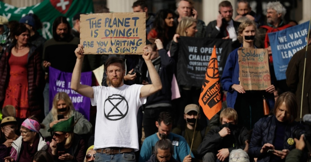 Extinction Rebellion climate change protesters hold placards calling for action on climate change during a rally in Trafalgar Square, London, Wednesday, Oct. 16, 2019. (AP Photo)