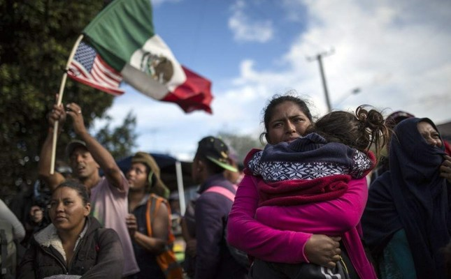 Honduran migrant holds her daughter amid a small group of migrants trying to make their way to the U.S., Nov. 22, 2018.