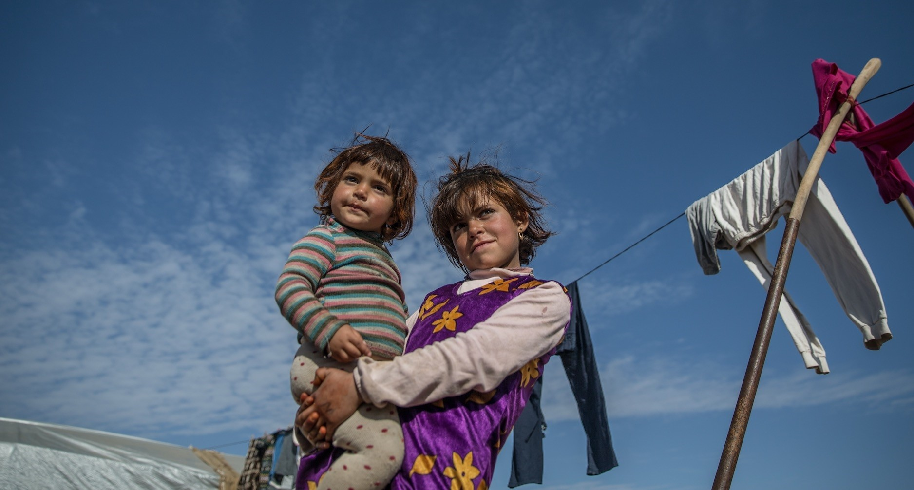 A Syrian girl holds a younger girl as the two pose near the tent they live in with their families in the southeastern city of u015eanlu0131urfa. The girlu2019s family  is among the Syrian refugees forced to flee Raqqa.