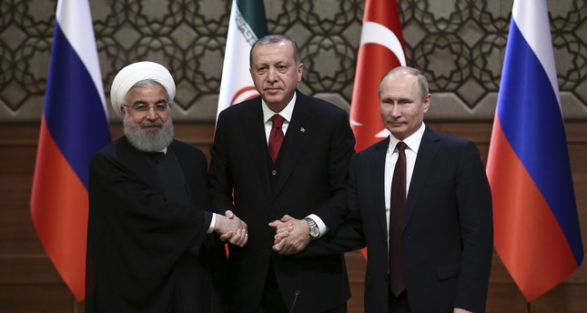 President Recep Tayyip Erdoğan (C), Iran's President Hassan Rouhani (L) and Russia's President Vladimir Putin (R) shake hands after a joint conference as part of a tripartite summit on Syria in Ankara, April 4.