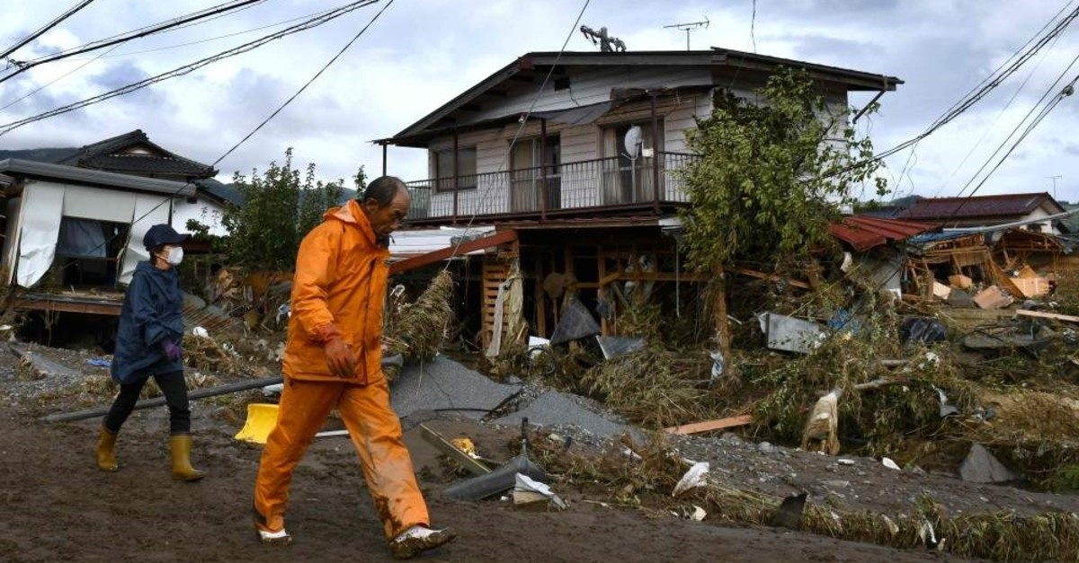 Residents walking past flood-damaged houses in Nagano, after Typhoon Hagibis hit Japan, Oct. 15, 2019. (AFP)