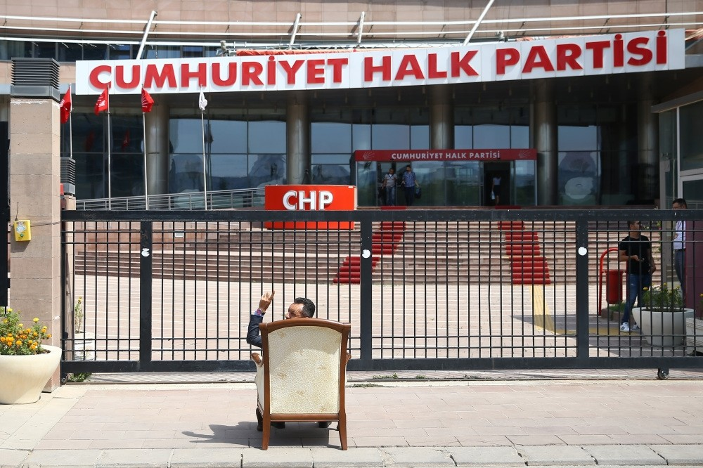 A party member protests Kemal Ku0131lu0131u00e7darou011flu's one-man rule in the party by sitting on a chair in front of the CHP headquarters in Ankara, Aug. 8.
