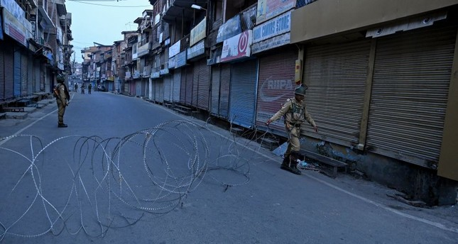 An Indian paramilitary soldier unfolds barbed wire to block a road during restrictions in Srinagar, Kashmir, Sept. 27, 2019.