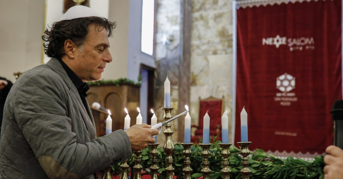 A Jewish man lights a Hanukkah menorah in Istanbul's Neve u015ealom Synagogue, Dec. 21, 2017.