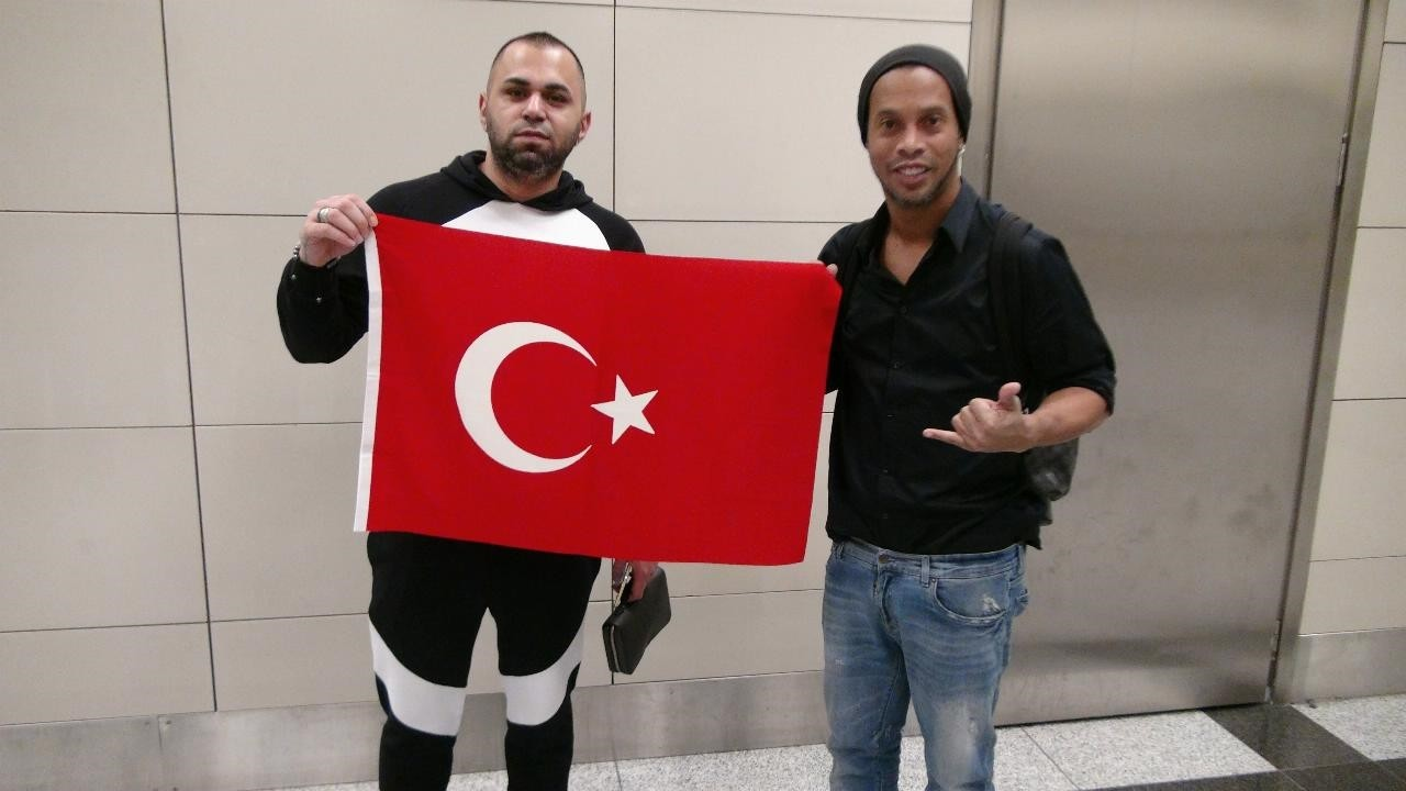 Ronaldinho poses with a Turkish fan at the airport.