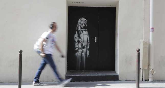 In this file photo taken on June 25, 2018 A man walks past an artwork by street artist Banksy in Paris on a side street to the Bataclan concert hall where a terrorist attack killed 90 people on Novembre 13, 2015. (AFP Photo)