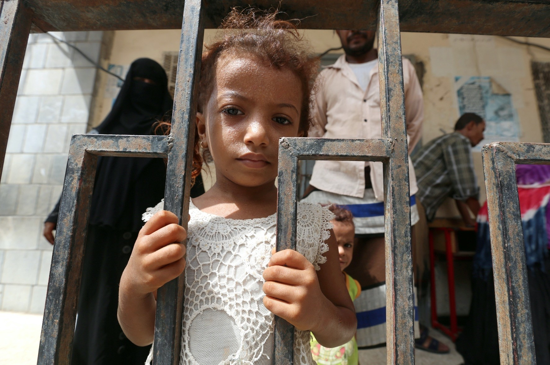 A girl stands behind a fence at a school to which she and her family have been evacuated from a village near Hodeidah airport, June 17.