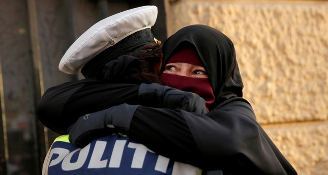 Ayah, 37, a wearer of the niqab weeps as she is embraced by a police officer during a demonstration against the Danish face veil ban in Copenhagen, Denmark, August 1, 2018. (Reuters Photo)