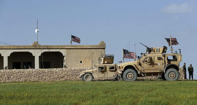 U.S. soldiers sit in front of a house that has been turned into an outpost on a road leading to the tense frontline between U.S.-backed YPG terrorists and Turkish-backed fighters in Manbij, March 29, 2018.