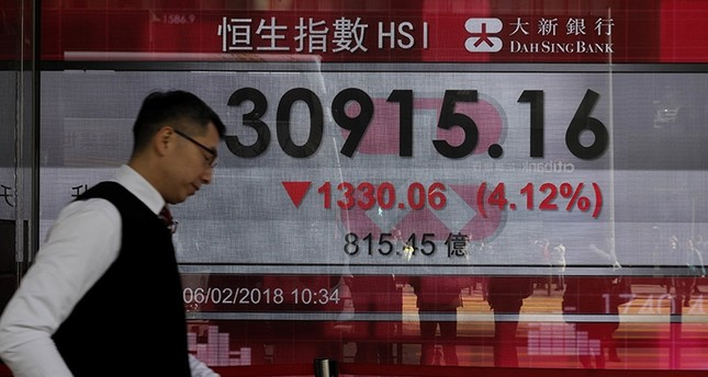 A man walks past a bank electronic board showing the Hong Kong share index at Hong Kong Stock Exchange Tuesday, Feb. 6, 2018. (AP Photo)