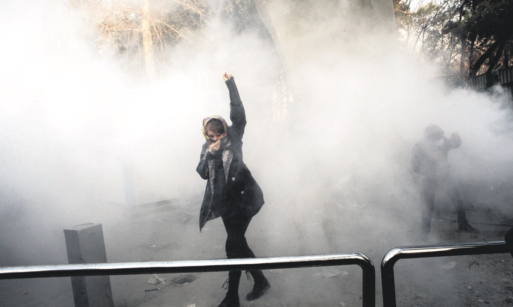 A university student attends a protest at the University of Tehran while a smoke grenade is thrown by anti-riot police, Tehran, Iran, Dec. 30.