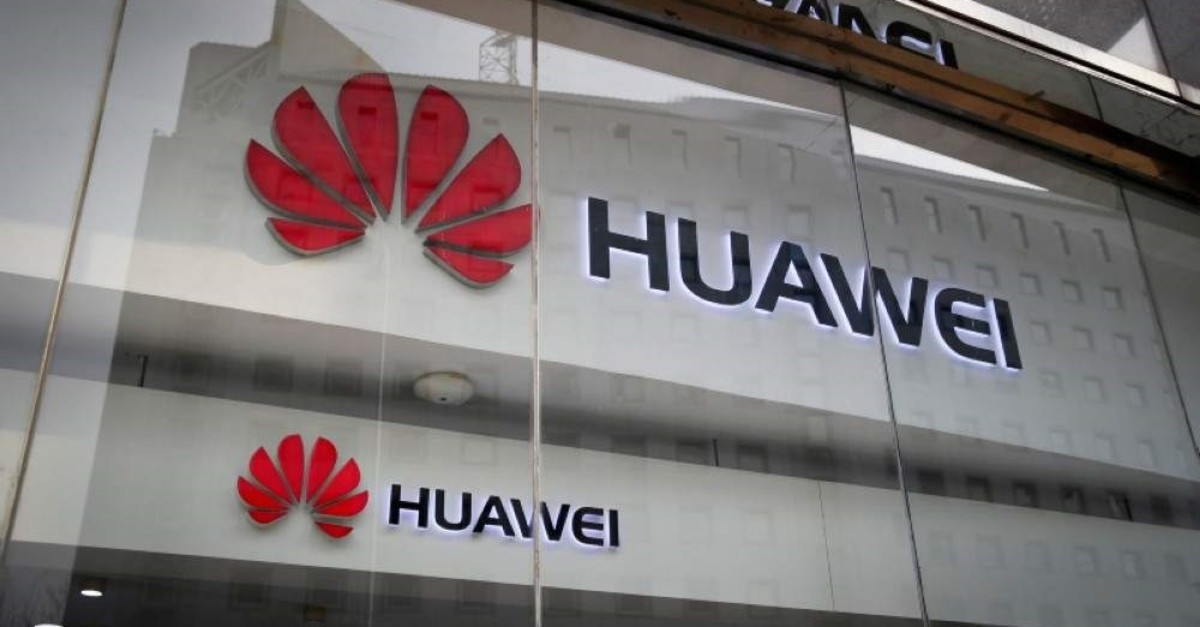 The logos of Huawei are displayed at its retail shop window reflecting the ministry of foreign affairs office in Beijing, Tuesday, Jan. 29, 2019. (AP Photo)