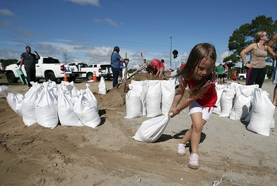 Chloe Heeden, 4, from Virginia Beach, Va., drags a sandbag to her father's car, Wednesday, Sept. 12, 2018, in Virginia Beach, Va., as Hurricane Florence moves toward the eastern shore. (AP Photo)