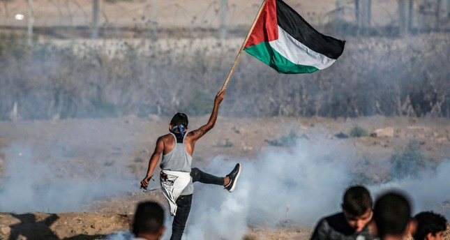 A protester raises a Palestinian flag during border protests, Gaza Strip, Sept. 6, 2019.