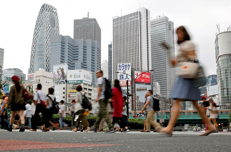 People cross a street in front of high-rise buildings in the Shinjuku district in Tokyo. (Reuters Photo)