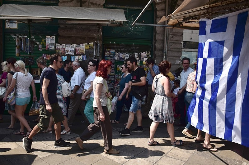 People walk past a Greek flag in central Athens on June 16, 2017. (AFP Photo)