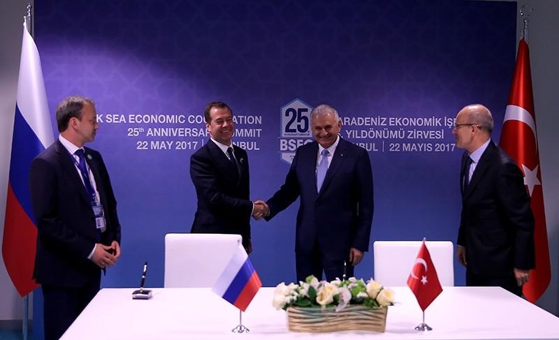 Prime Minister Binali Yu0131ldu0131ru0131m (CR) shake hands with his Russian counterpart Dmitry Medvedev (CL) alongside Deputy PM Mehmet u015eimu015fek and his Russian counterpart Arkady Dvorkovich during the BSEC's 25th anniversary summit in Istanbul (AA Photo)