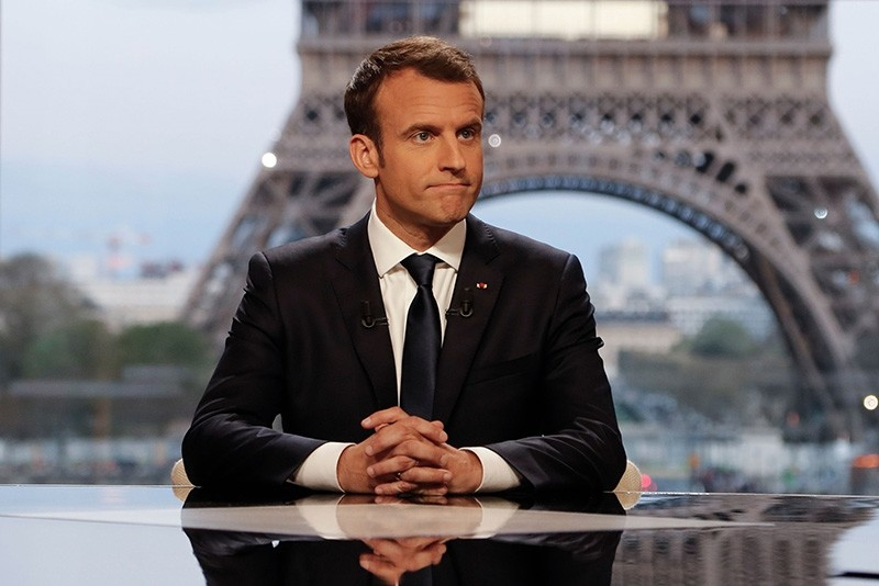 French President Emmanuel Macron (C) poses on the TV set before an interview with RMC-BFM and Mediapart French journalists at the Theatre national de Chaillot in Paris, on April 15, 2018. (AFP Photo)
