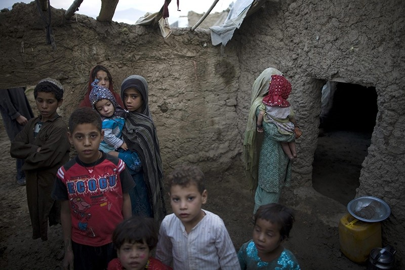 In this photo taken Wednesday, Aug. 4, 2010, children gather outside mud houses in a makeshift camp where displaced Pashto families from Helmand province, southern Afghanistan, live on the outskirts of Kabul, Afghanistan. (AP Photo)