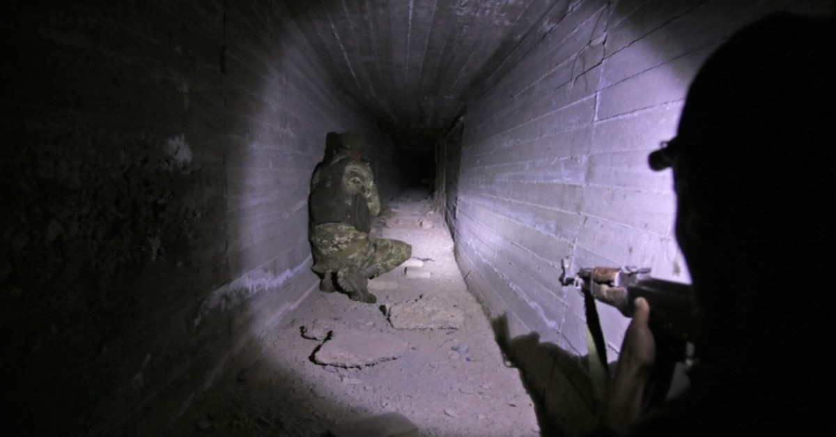 Turkish-backed Syrian fighters inspect a tunnel, said to have been built by Kurdish fighters, in the Syrian border town of Tal Abyad, on October 21, 2019. (AFP Photo)