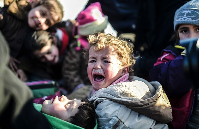 A Syrian child cries as Syrians fleeing the northern embattled city of Aleppo wait on February 5, 2016 in Bab-Al Salam, next to the city of Azaz near Turkish crossing gate in northern Syria. (AFP Photo)