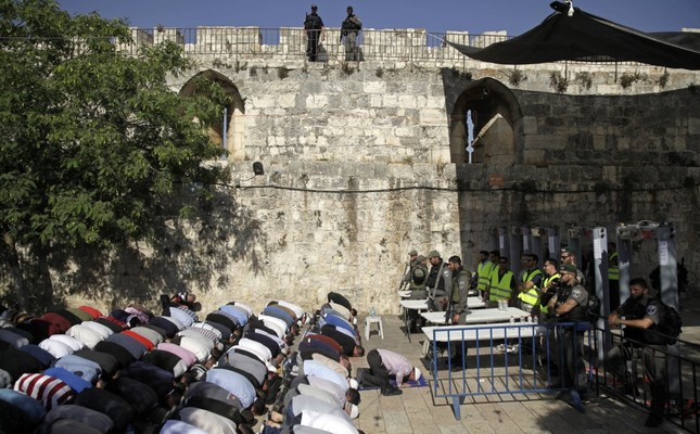 Israeli border police stand guard as Muslim men pray outside the Al-Aqsa Mosque compound, Jerusalem, July 16, 2019.