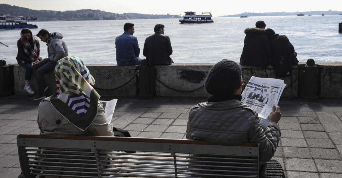 People sitting by the Bosporus in Istanbul read newspapers with news regarding the local elections, a day after the elections, Monday, April 1, 2019.