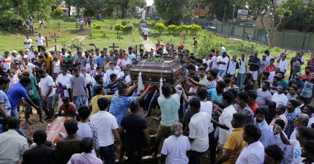 Sri Lankans prepare to bury the coffins carrying remains of Berington Joseph, left, and Burlington Bevon, who were killed in the Easter Sunday bombings in Colombo, Sri Lanka, Tuesday, April 23, 2019. (AP Photo)
