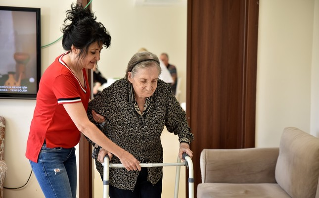 A carer helps an elderly woman at a retirement home for senior citizens in the western city of Eskişehir's Tepebaşı district, Sept. 20, 2019.