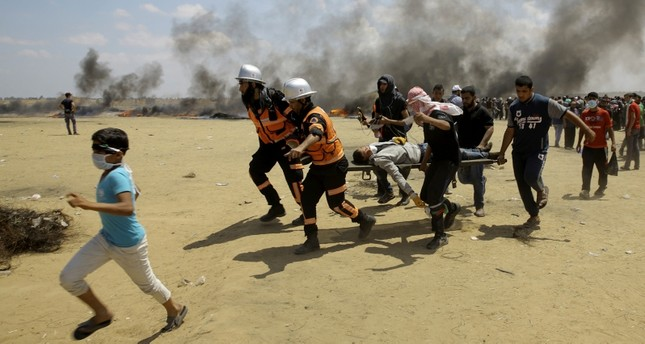 In this Monday, May 14, 2018 file photo, Palestinian medics and protesters evacuate a wounded youth during a protest at the Gaza Strip's border with Israel, east of Khan Younis, Gaza Strip. (AP Photo)