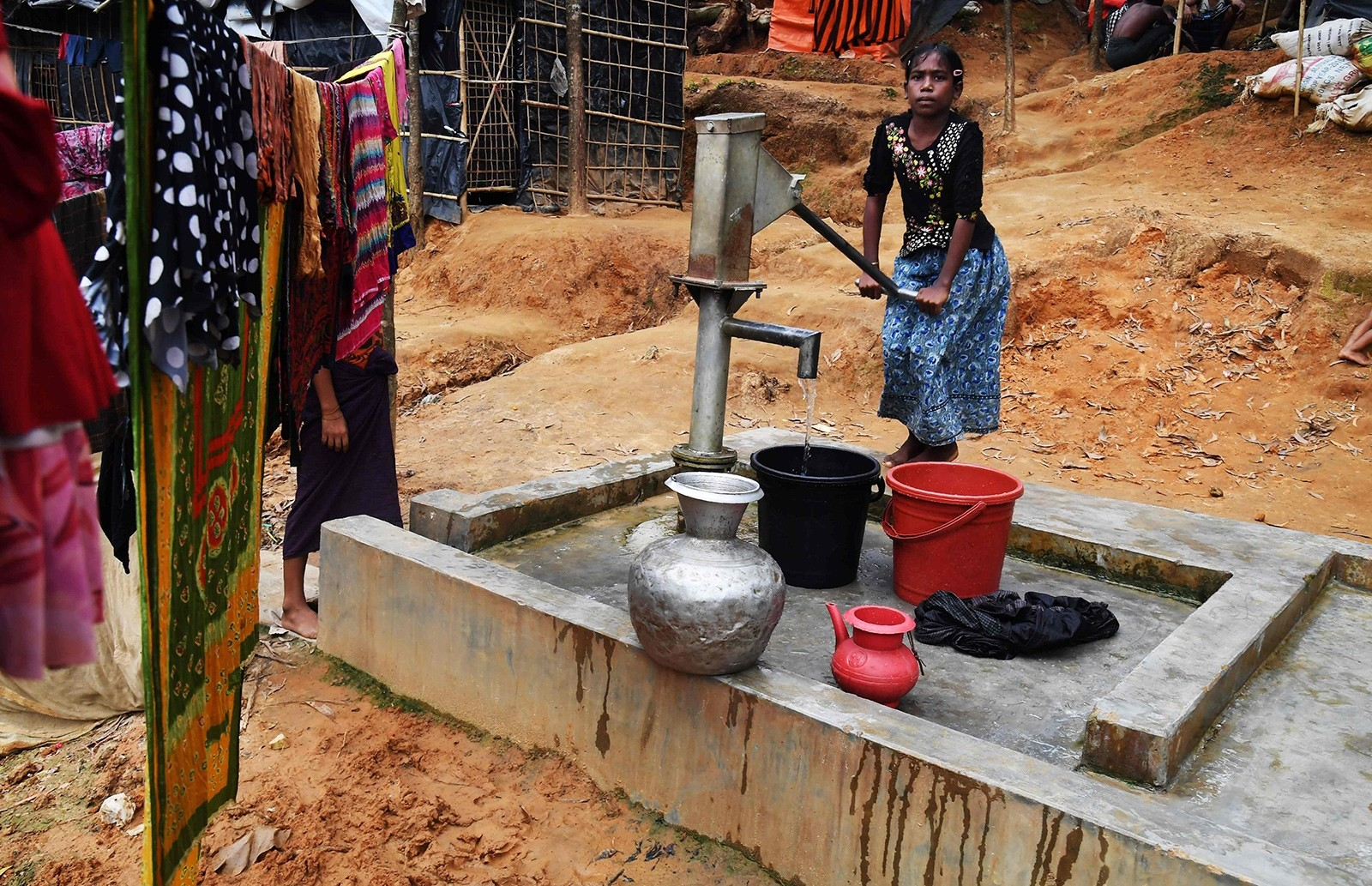 This picture taken November 4, 2017 shows ten-year-old Rohingya refugee Tahera Begum collecting water from a hand-pump at the Balukhali refugee camp in Bangladesh's Ukhia district (AFP Photo)