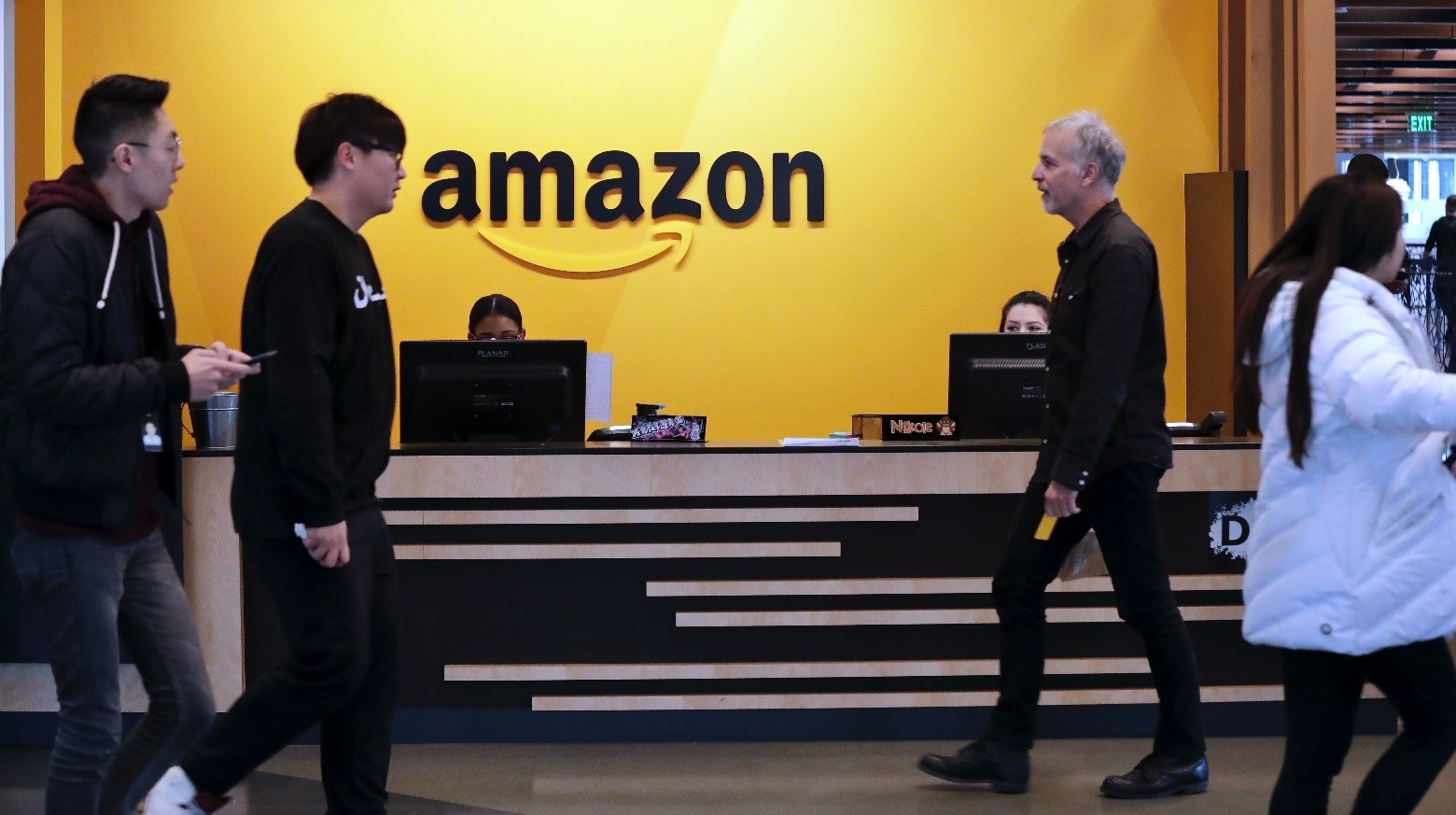Employees walk through a lobby at Amazonu2019s headquarters, Seattle, Nov. 13.
