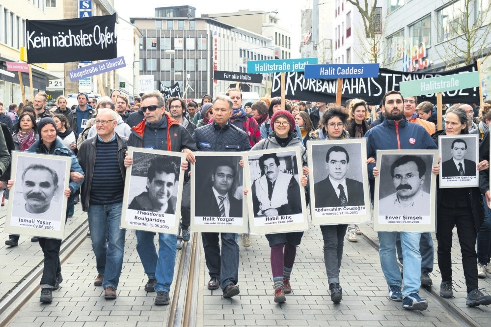 Demonstrators walk in Kassel, Germany holding posters of people killed by the NSU, April 6, 2017.