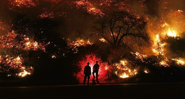 Firefighters monitor a section of the Thomas Fire along the 101 freeway on December 7, 2017 north of Ventura, California. (AFP Photo)