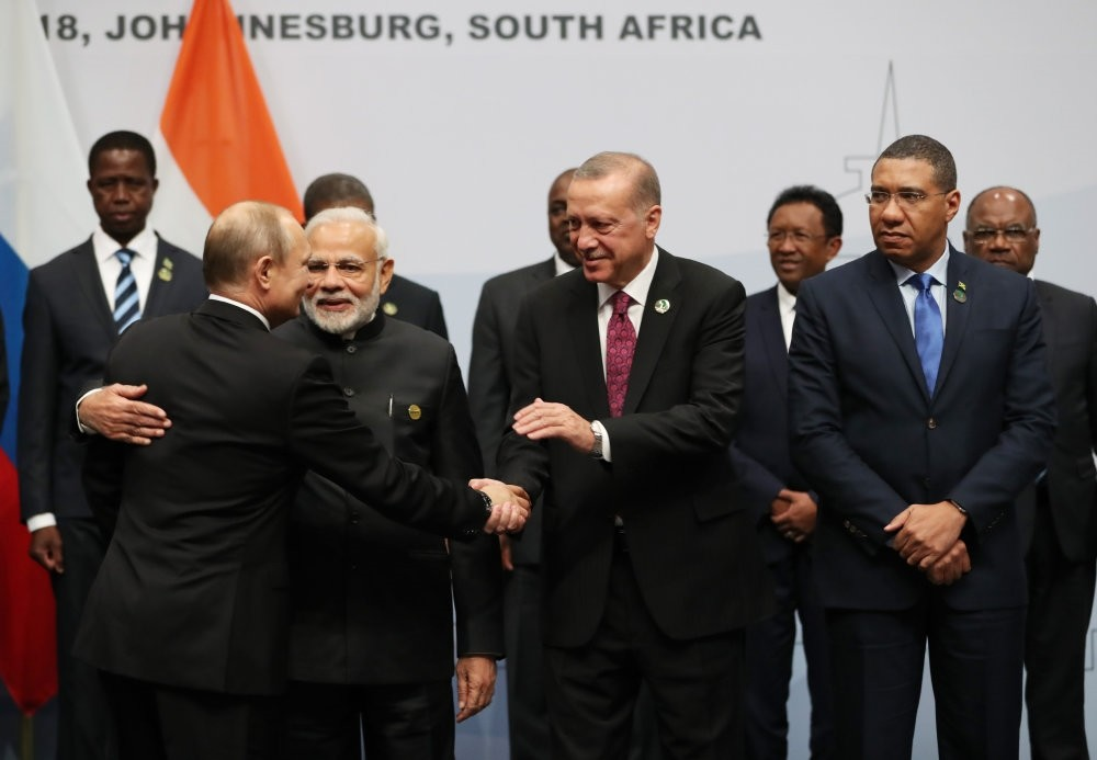 President Recep Tayyip Erdou011fan shakes hands with Russian President Vladimir Putin (L) next to Indian Prime Minister Narendra Modin (C) before taking a group picture at the BRICS summit meeting, Johannesburg, July 27.