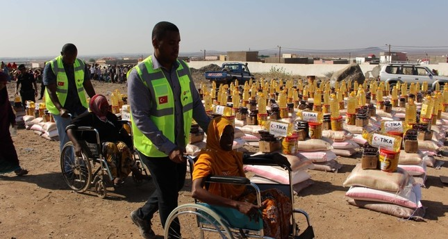 TİKA workers help women in wheelchairs as they arrive to receive aid in Djibouti's Tadjourah region, June 12, 2019.