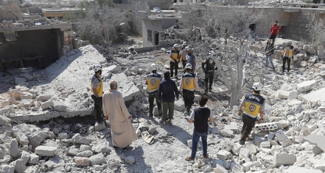 Members of the Syrian Civil Defence (White Helmets) and civilians gather following a reported regime airstrike on the village of Kafriya, in Syria's Idlib province, on July 13, 2019. (AFP Photo)