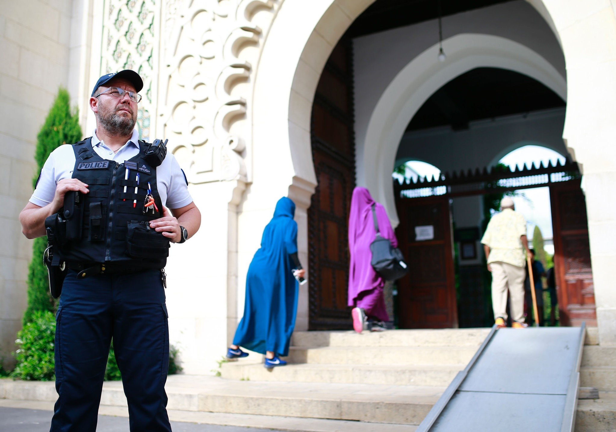 A police officer stands guard as people enter the Grand Mosque of Paris on May 27, 2017 in Paris, at the start of the holy month of Ramadan.