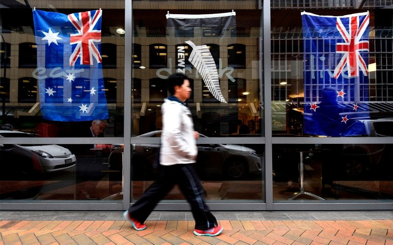 This file photo taken on October 29, 2015 shows a pedestrian walking past a bar window displaying New Zealand's national flag (R) and Australia's national flag (L) in Wellington. (AFP Photo)