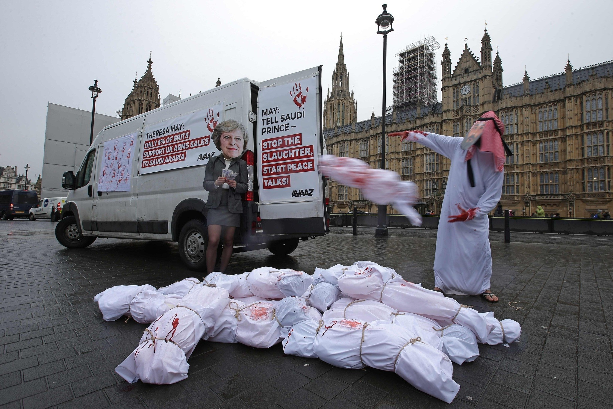Demonstrators wearing masks depicting Britain's Prime Minister Theresa May (L) and Saudi Arabia's Crown Prince Mohammed bin Salman protest outside of the Houses of Parliament in London on March 7, 2018. (AFP Photo)