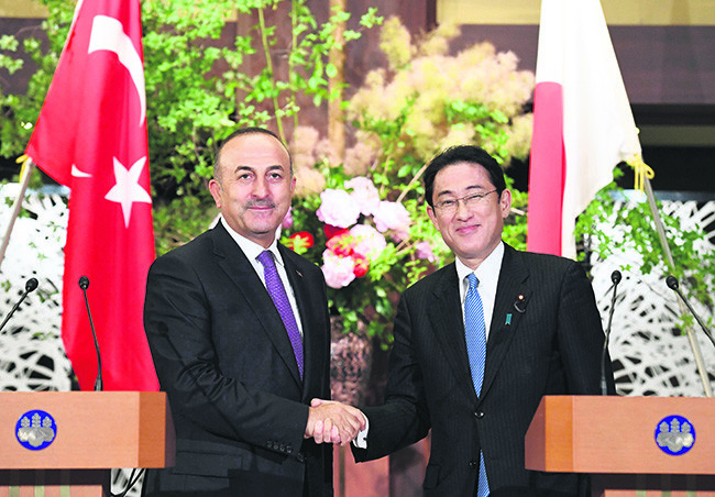 Foreign Minister Mevlu00fct u00c7avuu015fou011flu (L) shakes hands with his Japanese counterpart Fumio Kishida (R) during their joint remarks announcement at the foreign ministryu2019s Iikura guesthouse in Tokyo on June 21.