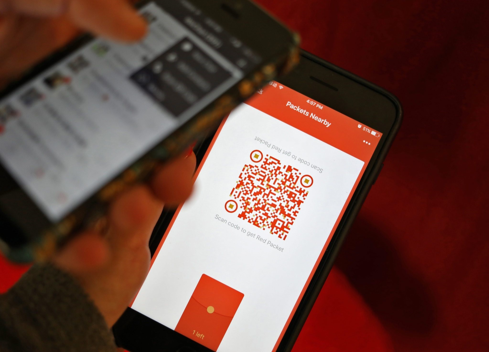 A photo illustration of a WeChat user scanning a QR code to retrieve a digital red envelope on the WeChat app on a mobile phone during the Chinese New Year period in Beijing, China, 30 January 2017. (EPA Photo)