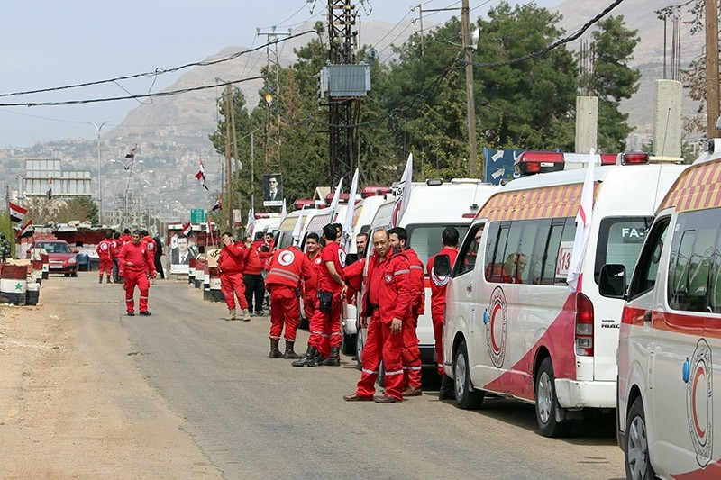Syrian Red Crescent ambulances stand in wait to enter the besieged opposition-held town Zabadani, northwest of Damascus, on April 12, 2017. (AFP Photo)
