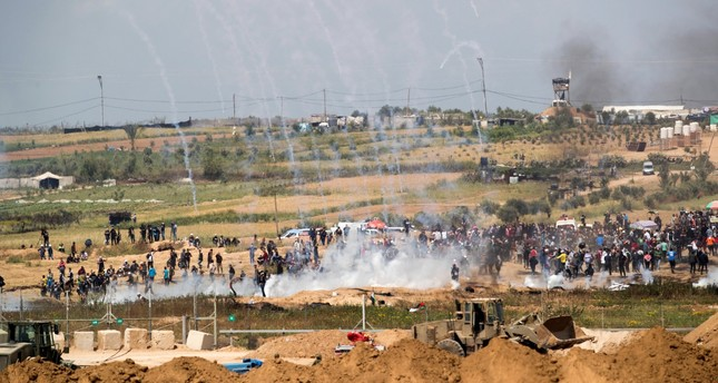 Tear gas canisters fired by Israeli forces fall around Palestinians from Gaza during a protest march at the Israeli Gaza border near Nahal Oz, facing the Gaza neighborhood of Shajaiyaon, April 6, 2018. (EPA Photo)