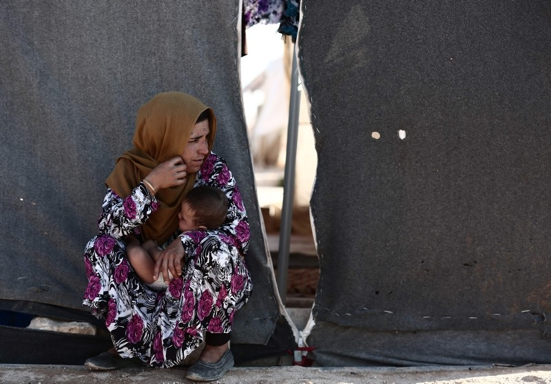 A woman carries a child as she sits in front of a tent at a camp for the displaced from the rebel-held Syrian province of Idlib, at the village of al-Ghadfa, southeast of the province on September 2, 2018. (AFP Photo)